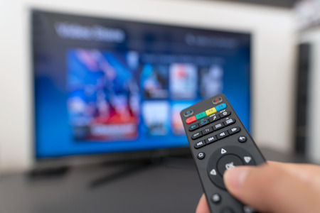 Multimedia streaming concept. Hand holding remote control. Video on demand Stock Photo