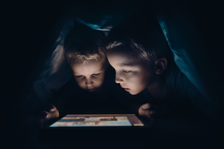 Two kids with tablet computer in a dark room. Protection of children against content from the internet concept