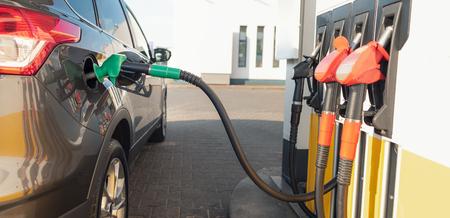 灰色の車の燃料タンクのガスポンプノズル。ガソリンスタンドで車両に燃料を補給する 写真素材