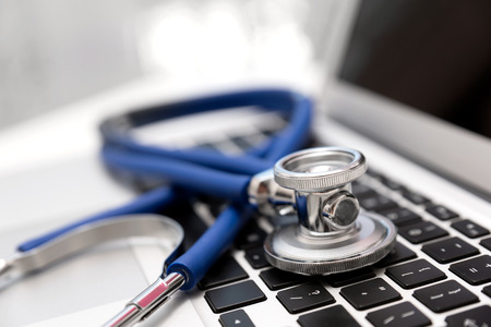 Stethoscope on laptop keyboard. Health care or IT security concept