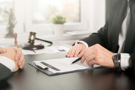 Männlicher Anwalt, der mit Vertragspapieren arbeitet. Anwalt oder Richter konsultieren, Treffen mit dem Kunden. Rechts- und Rechtsdienstleistungskonzept