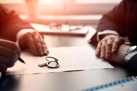 Agente inmobiliario que firma un contrato de compraventa de casa. Dos hombres sentados en el escritorio, póliza de seguro de hogar sobre préstamos hipotecarios, concepto de agente de seguros