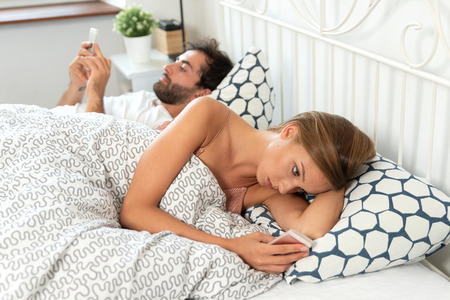 Young couple with smartphones in their bed. Bad relationship concept