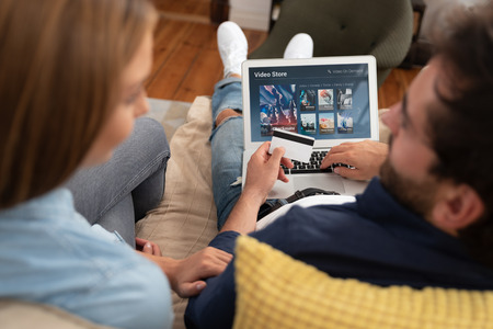 Couple using laptop for watching movie on VOD service. Video On Demand television subscription buy with credit card Zdjęcie Seryjne