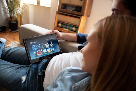 Pareja usando tableta digital para ver películas en el servicio VOD. Video On Demand televisión internet stream concepto multimedia