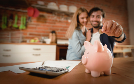 Happy couple inserting coin in piggybank. Home budget, family finance concept. Wide photo with space for your text Zdjęcie Seryjne