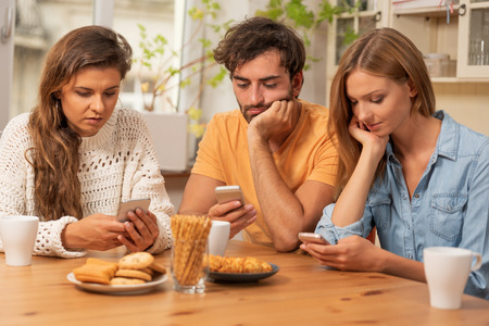 Friends sitting in the kitchen and watching on their phones. Internet browsing, and technology addiction concept Zdjęcie Seryjne