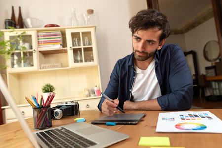 Graphic designer working on digital tablet. Freelancer working at home.