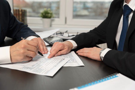 Tax advisor helps to complete US 1040 tax form. Businessmen working in a tax office Фото со стока