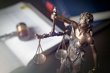 Lady justice, themis, statue of justice on books background. Law concept with justice figurine in library
