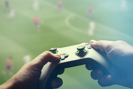 Man is playing on the console. Man holding gamepad and playing soccer game Zdjęcie Seryjne