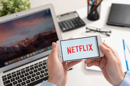 Wroclaw, Poland - JAN 31, 2019: Man holding smartphone with Netflix logo. Netflix is a global provider of streaming movies and TV series