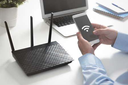 Wireless router or access point. Man using smartphone with wireless symbol