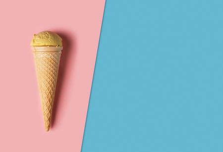 Ice cream with wafer cone on pink and blue background. Top view flat lay with copy space composition