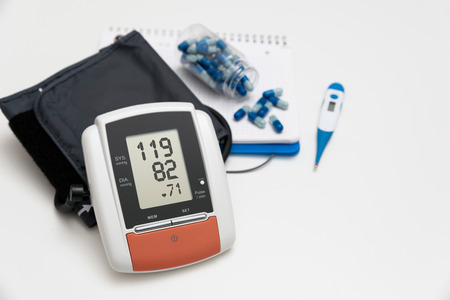 Digital blood pressure monitor on white background