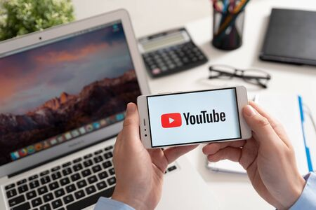 Wroclaw, Poland - JAN 31, 2019: Man holding smartphone with Youtube logo. Youtube is most popular video service developed by Google