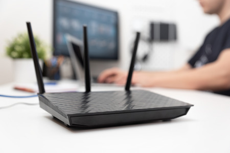 Modern dual band wireless router. Man working in the background. Fast and wireless internet concept. Zdjęcie Seryjne