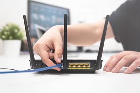 El hombre conecta el cable de Internet a la toma del enrutador. Concepto de internet rápido e inalámbrico