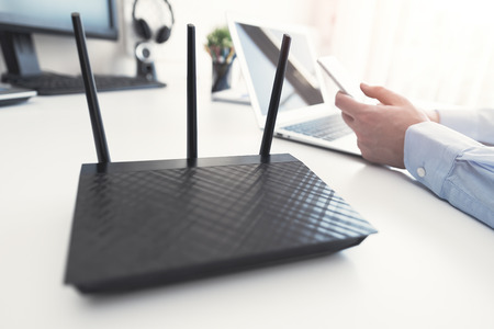 Wireless router concept. Man using smartphone in background