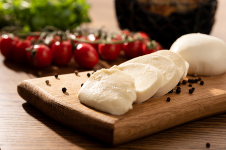 Mozzarella cheese on wooden chopping board. Cherry tomatoes in background. Wooden table with Italian food composition