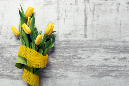 Spring flowers, yellow tulips with ribbon background. Top view with copy space. Zdjęcie Seryjne