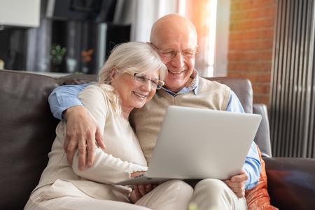 Coppia senior navigando in internet insieme. Pensionati che usano un computer portatile a casa Archivio Fotografico