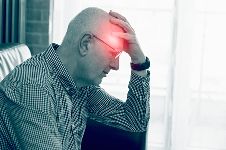 Older man has a headache. Pain, red point effect.