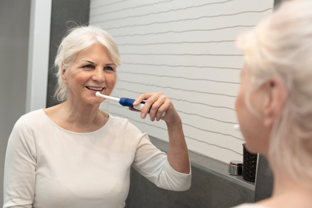Cute mature woman brushing teeth. Electric toothbrush used by senior woman.