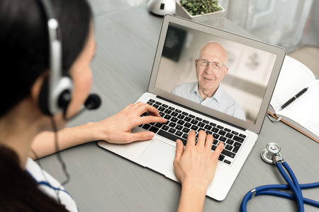 Doctor talking with a senior patient. Telemedicine concept Zdjęcie Seryjne