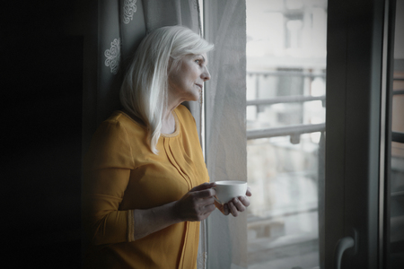 Depressed senior woman near window at home