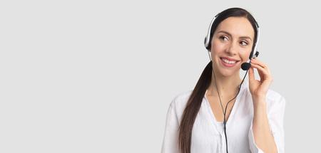 Consultor de call center en auriculares sobre fondo gris. Operador de la línea de ayuda con auriculares