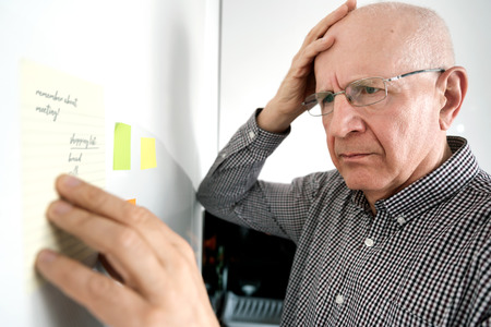 Confused senior man with dementia looking at notes on the fridge