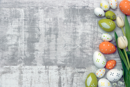 Easter eggs and spring flowers background. Top view with copy space.