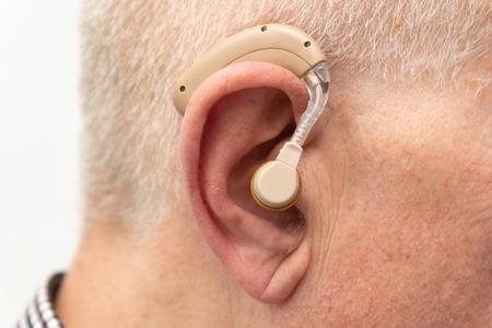 Aide auditive dans l'oreille du vieil homme âgé. Aîné utilisant l'aide auditive moderne Banque d'images