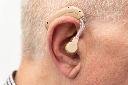 Hearing aid in the ear of aged old man. Senior using modern hearing aid Reklamní fotografie - 120477924
