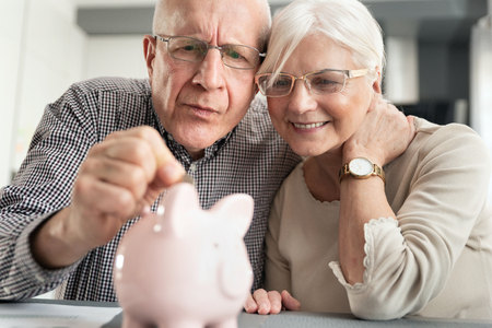 Senior couple puts the coin into the piggybank. Retirement savings concept.