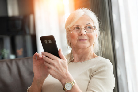 Portrait of elegant senior woman with smart phone. Lifestyle photo of pension woman.