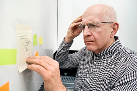 Oudere man kijken naar notities. Vergeetachtige senior met dementie, geheugenprobleem, gezondheidsconcept Stockfoto