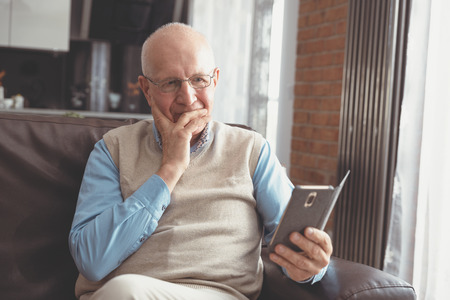 Senior man using a smartphone and smiling while sitting on couch at home. Zdjęcie Seryjne