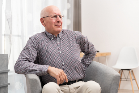 Senior man suffering from backache sitting on armchair at home