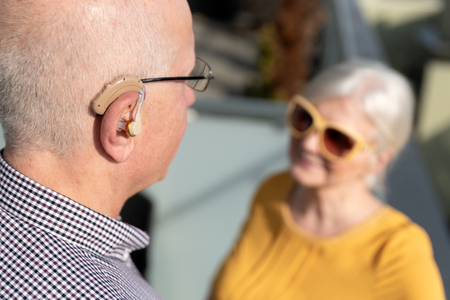 Elderly, deaf man uses a hearing aid. Two people conversation Imagens