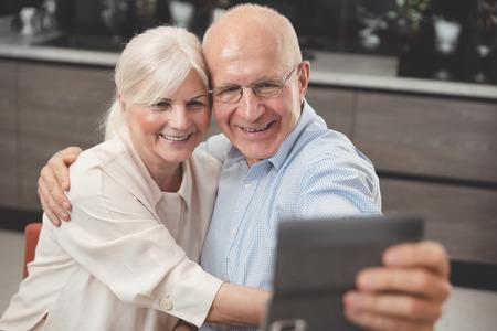 Cheerful senior couple taking selfie at home Zdjęcie Seryjne