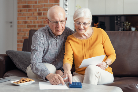 Senior couple paying bills together with calculator. Couple doing some paperwork and calculations at home