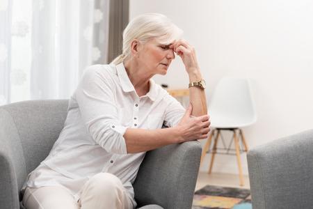 Older woman has a headache. Senior healthcare concept