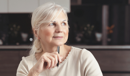 Cheerful senior woman portrait. Pensioner woman holding a pen, sits at home and looks at the window. Concept of a happy retirement