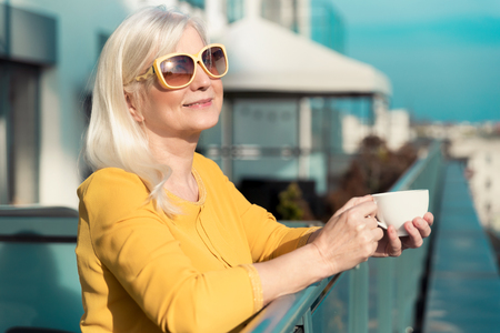 Cheerful, elderly woman enjoying sunny day on balcony. Senior people activity on retirement concept
