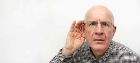 Senior suffering from deafness. Man asks to repeat the question. Wide copy space image for web banner background