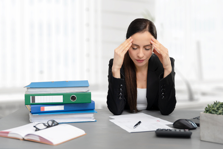 Tired businesswoman in the office. Young female employee unhappy with excessive work.