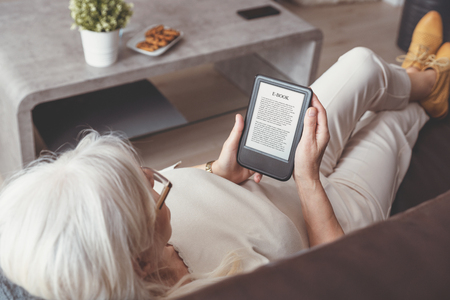 Senior woman sitting by the window, reading an e-book on digital tablet device Imagens