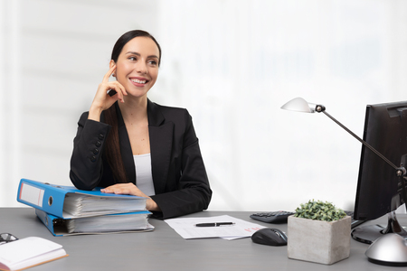 Female accountant sitting at desk in office. Portrait of young smiling bookkeeper